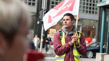 junger Mann mit Warnweste und Fahne
