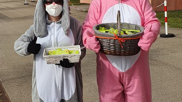 2 Personen in grauen und rosa Hasenkostümen mit Körben voller ver.di Ostergrußkarten