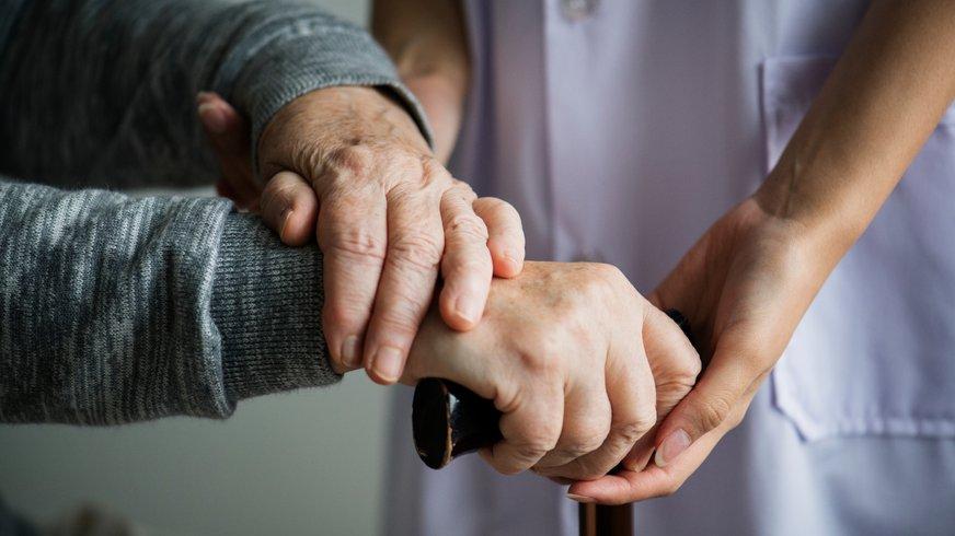 Frau hält die Hand einer älteren Person