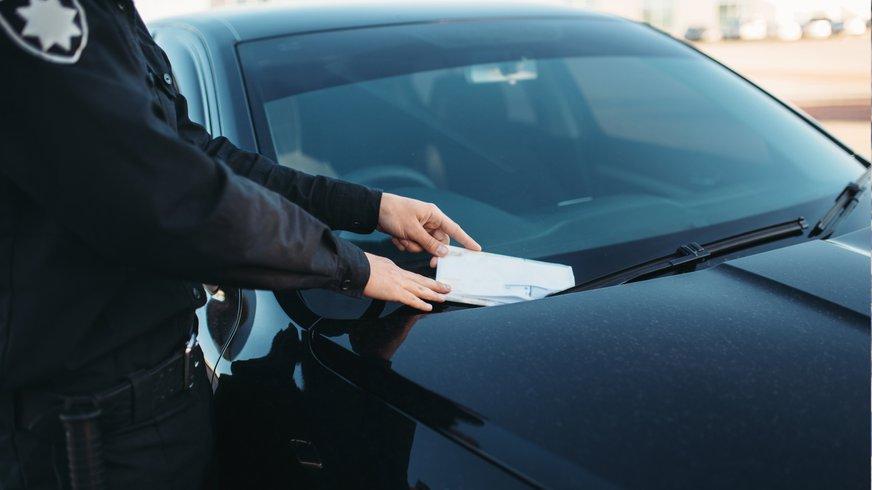 Mitarbeiter des Ordnungsdienstes steckt einen Straffzettel unter den Scheibenwischer eines Autos