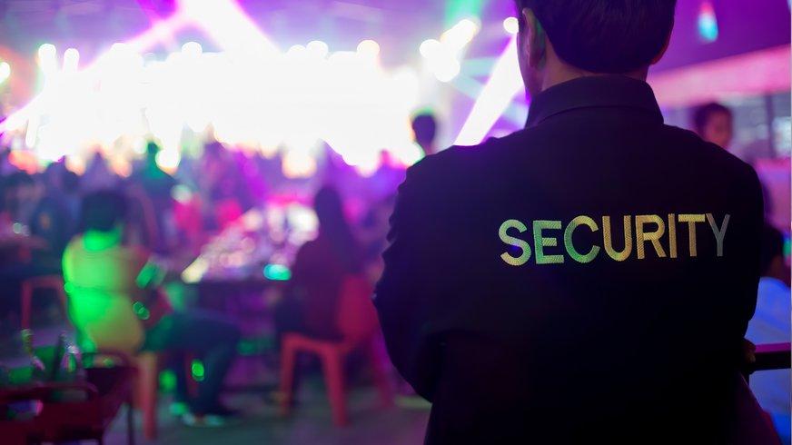 Security Mitarbeiter steht vor einem Club Raum und beobachtet die Gäste