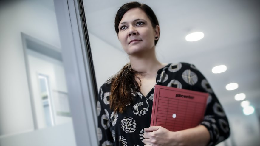 Mitarbeiterin im Jobcenter geht mit einer Fallakte durch den Flur