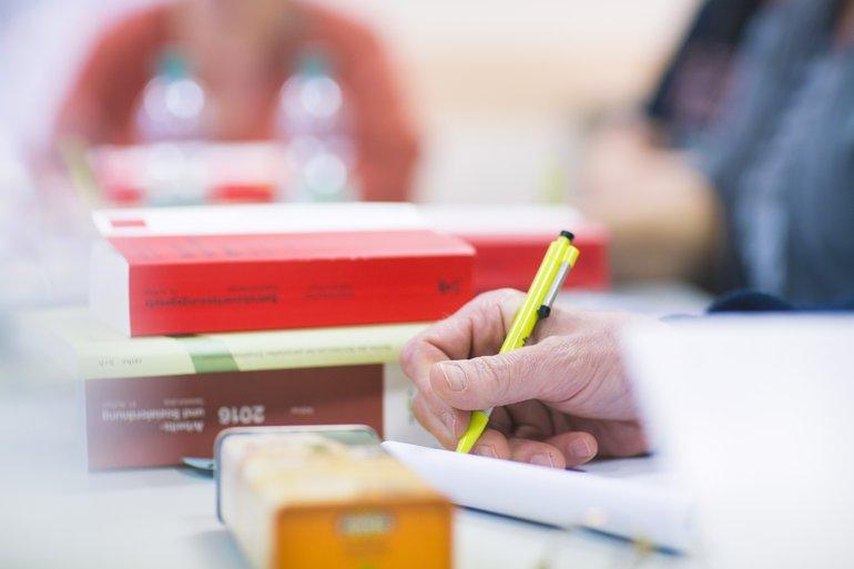 Person schreibt während eines Seminars mit. Ein Gesetzbuch liegt auf dem Tisch.